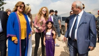 Shakira posing for a picture with a girl dressed in traditional Lebanese clothing during her visit